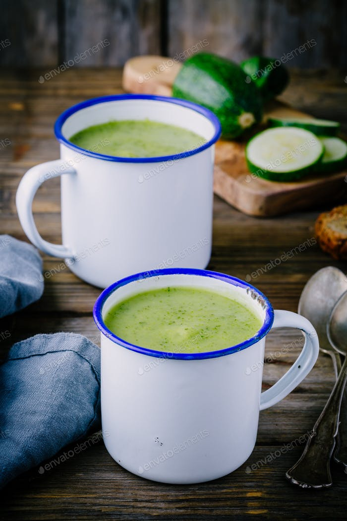 homemade green zucchini cream soup with parsley in mugs
