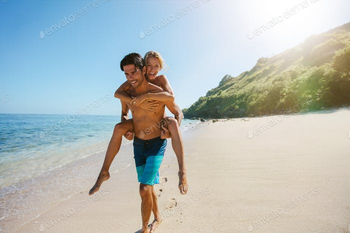 Man carrying girlfriend on his back along the beach