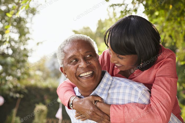 Senior black couple piggyback, looking at each other