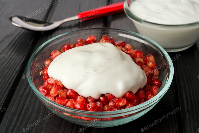 group of pomegranate grains with yogurt in glass bowl on black wood