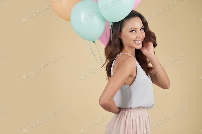 Hilarious girl hiding helium balloons behind back