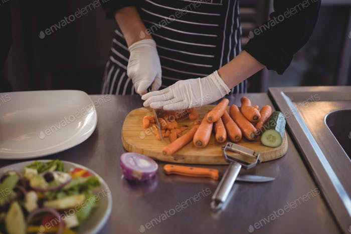 Midsection of female chef cutting carrots on board in kitchen
