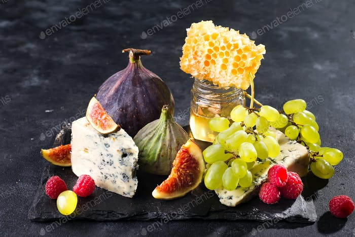delicious cheese with fresh honey, figs slice and grapes on dark slate board