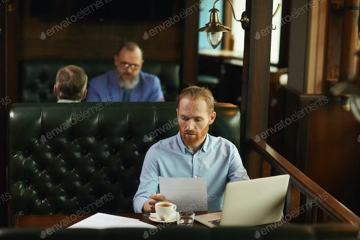 Mature man working in cafe