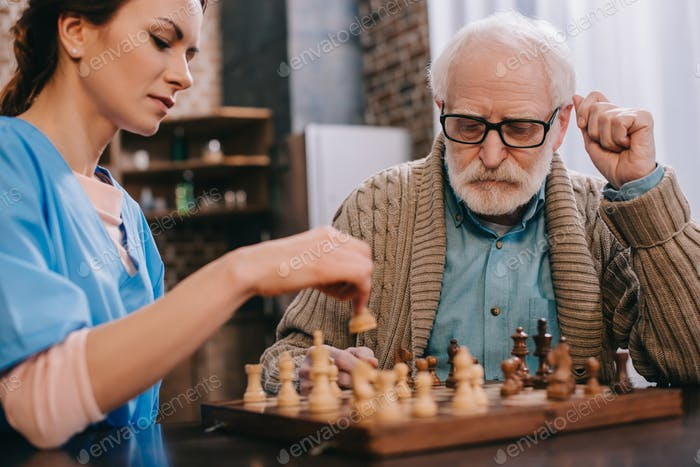 Nurse and senior man playing chess