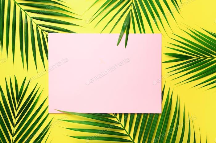 Tropische Palmblätter auf pastellgelbem Hintergrund mit Papierkarte Notiz. Minimales Sommerkonzept