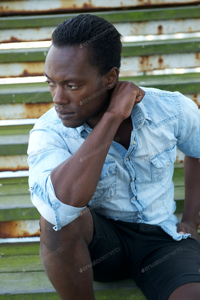 Handsome black male model sitting outdoors