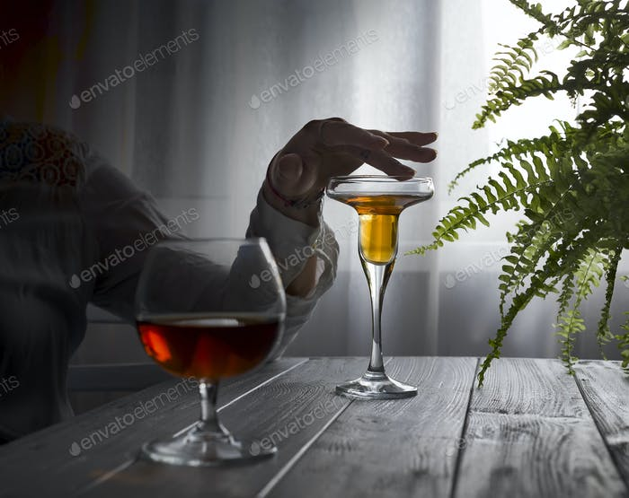 Young beautiful woman in depression, drinking alcohol on dark background