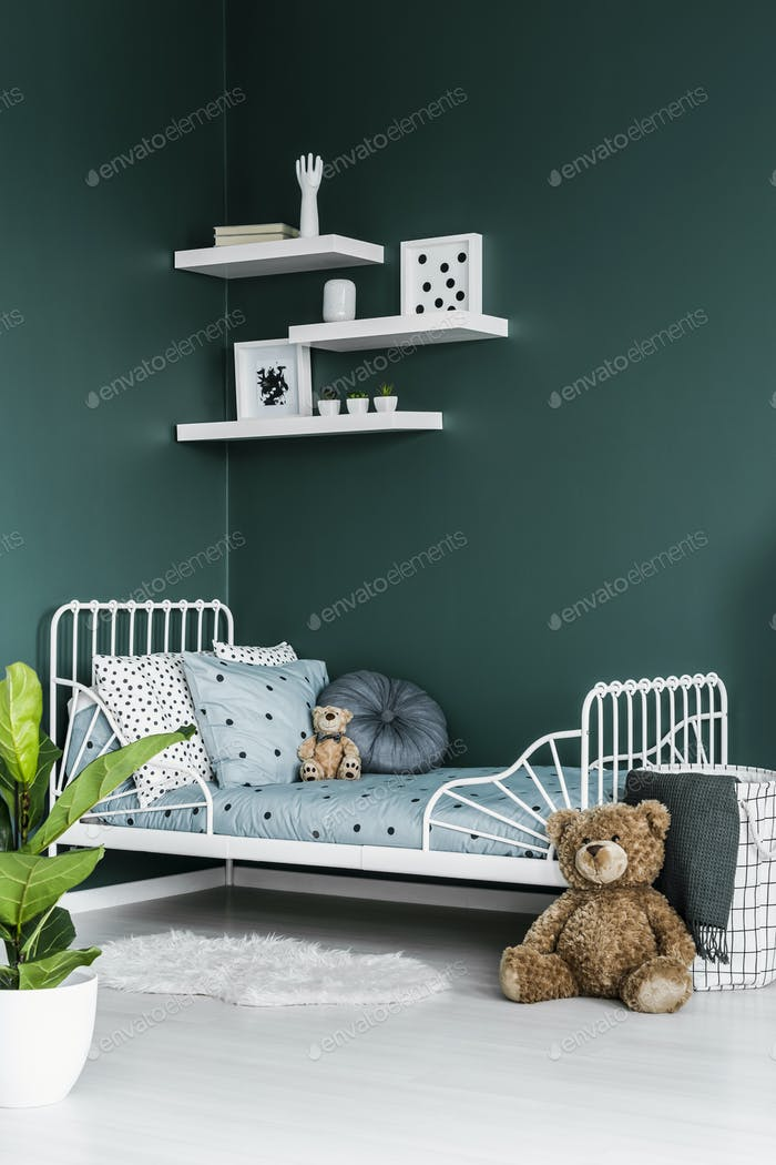 Teddy bear toy by a white twin bed in a dark green bedroom inter