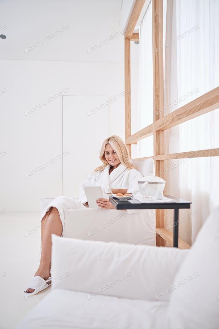 Спа женщина-клиент смотрит на свой гаджет
