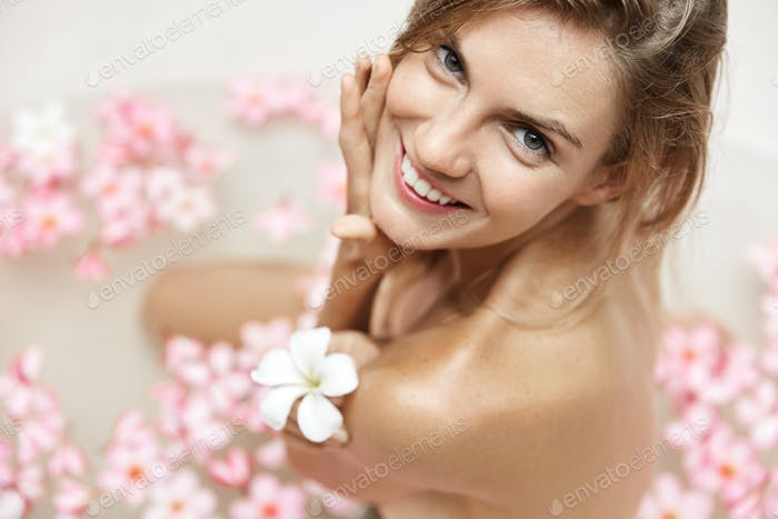 Close up portrait of happy well groomed female with soft skin, sits in bathtub filled with hot water