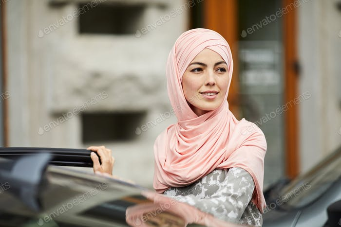 Muslim woman getting in her car