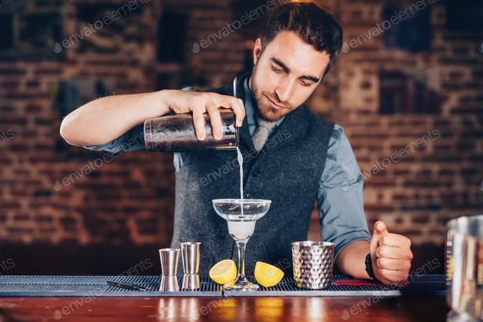 Close up of barman hands adding ice and tequila to modern urban cocktails.