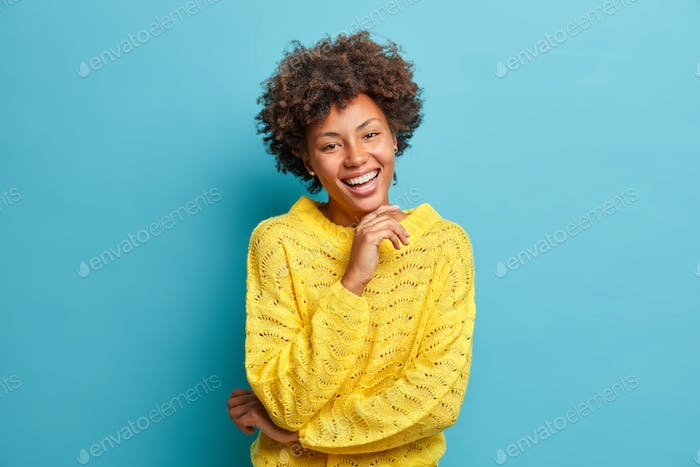 Successful happy dark skinned curly woman smiles broadly with white perfect teeth and feels very gla