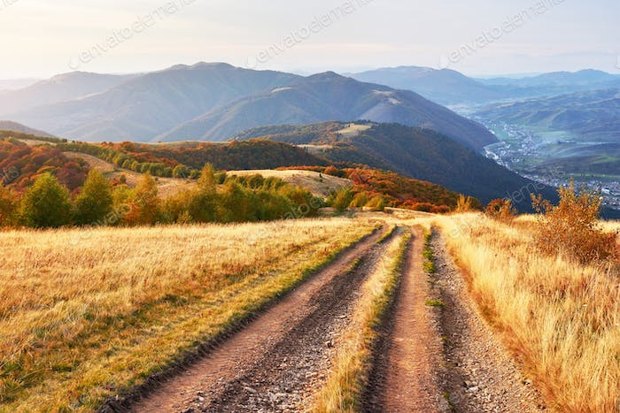 road in the mountains. Wonderful autumn mountain landscape. majestic, overcast clouds in sunlight