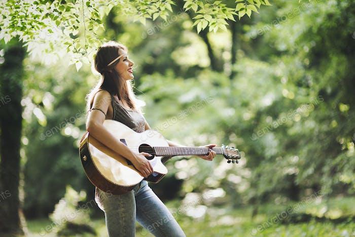 Schöne Frau Gitarre spielen in der Natur