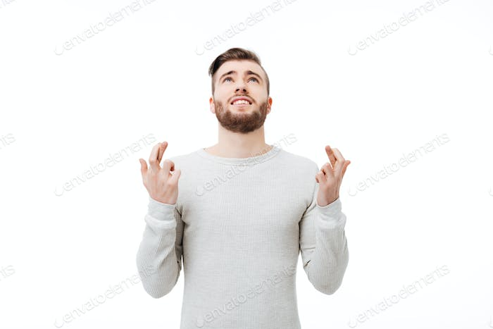 Young man praying with finger crossed gesture looking up isolated