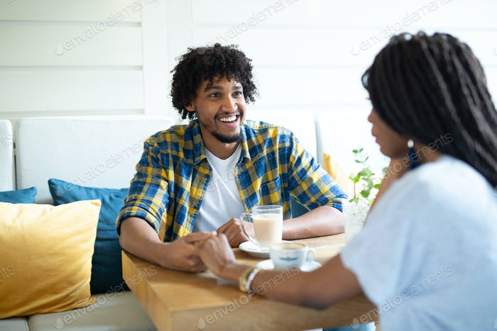 Flirting in a cafe. Beautiful loving couple sitting in a cafe enjoying in coffee and conversation