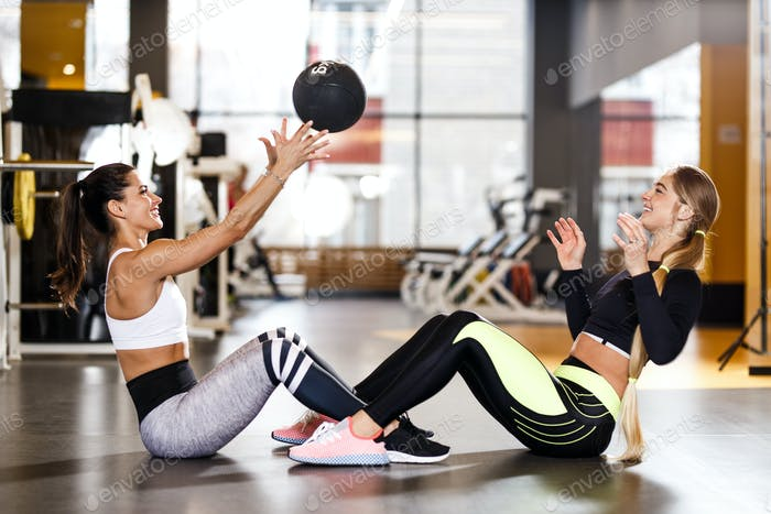 Two young athletic girls dressed in sportswear are doing together sport exercises for press with