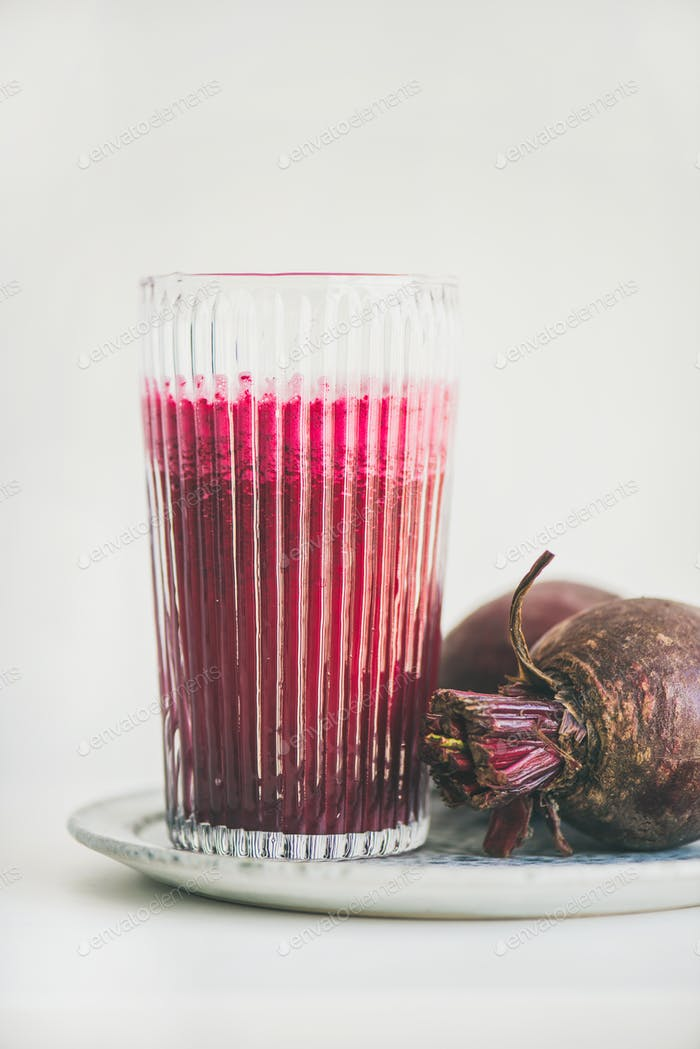 Fresh morning detox beetroot smoothie in glass, white background
