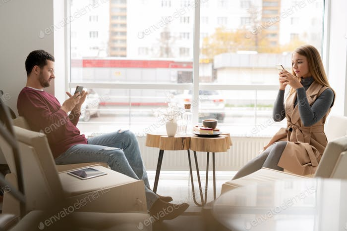 Two millennials in casualwear sitting against window and scrolling in gadgets