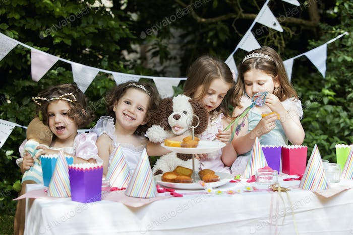 Group of young girls dressed up at a garden party.