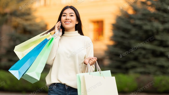 Asiática chica hablando en teléfono en el centro de la ciudad