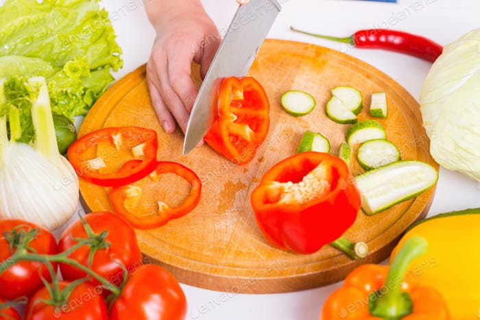 Cutting vegetables. Close-up of woman cutting vegetable on the cutting board