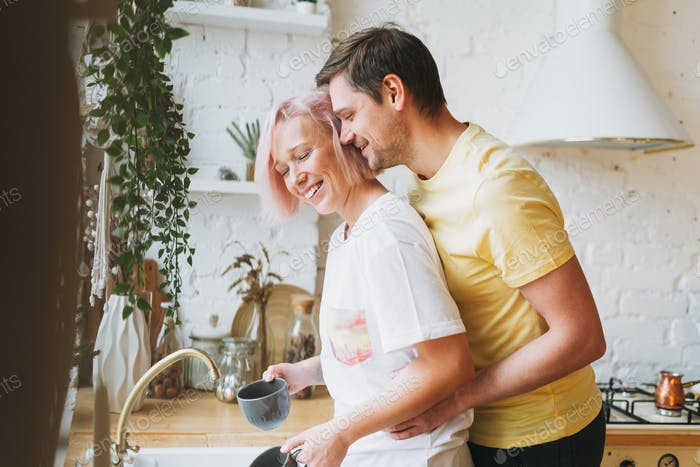 Young beautiful couple happy family having fun and wash dishes in bright kitchen at home