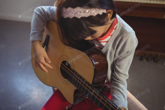 High angle view of girl practicing guitar