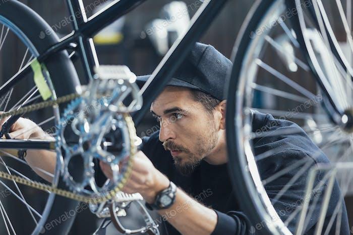 Artesano serio mirando la cadena de bicicletas