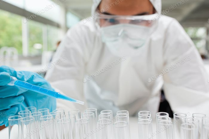 Protected scientist dropping a blue liquid in a test tube