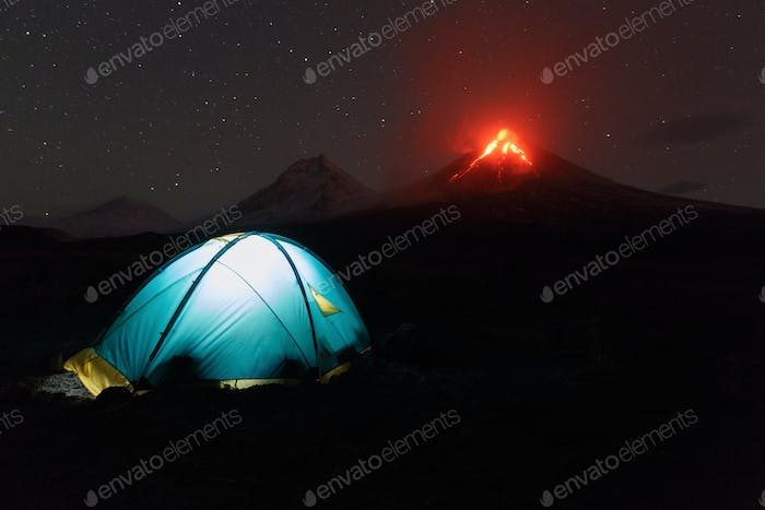 Illuminated Tourist Tent at Night on Background Erupting Volcano