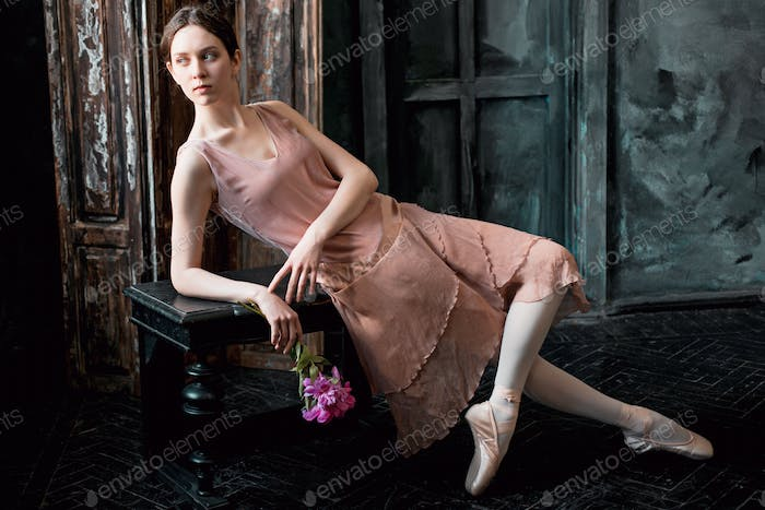 Young and incredibly beautiful ballerina is posing in a black studio