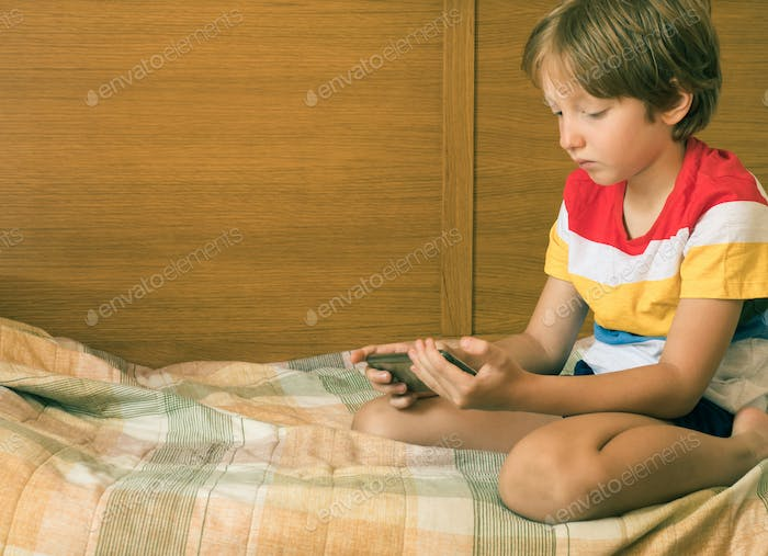 Little blonde boy playing games at smartphone