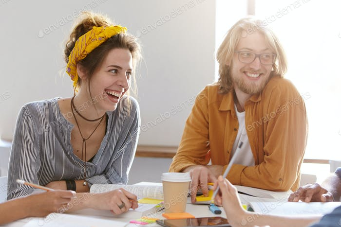 Pleased female in shirt and yellow scarf on head and bearded male with glasses sitting at their work