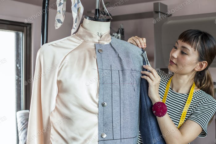 Japanese female fashion designer working on a garment on a dressmaker's model in a studio.