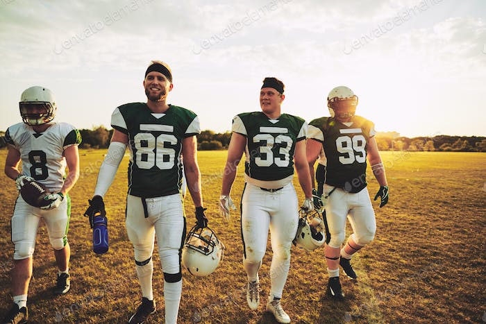 Smiling team of American football players walking off a field