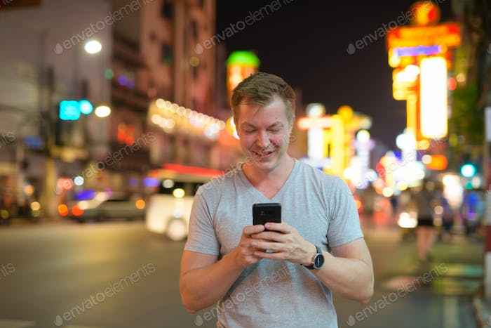 Young happy tourist man smiling while using phone in the streets of Chinatown at night