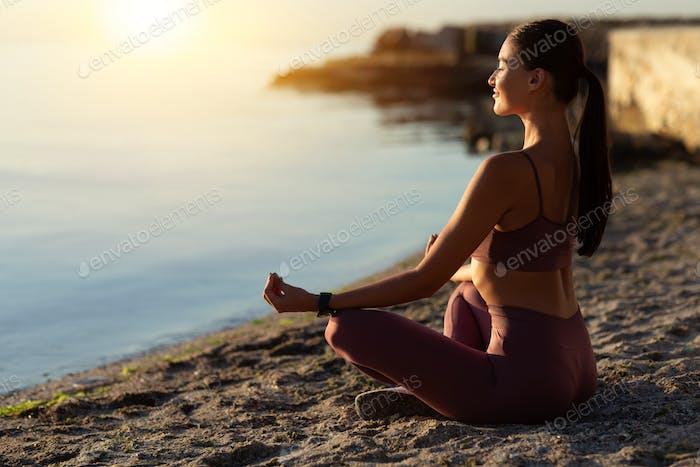 Weiblicher Yogi sitzt in Lotus-Pose und meditiert