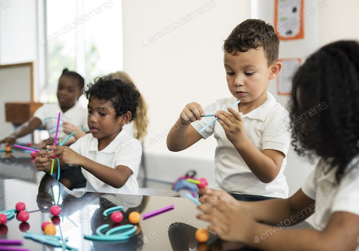 Kindergarten students holding learning structures from toys