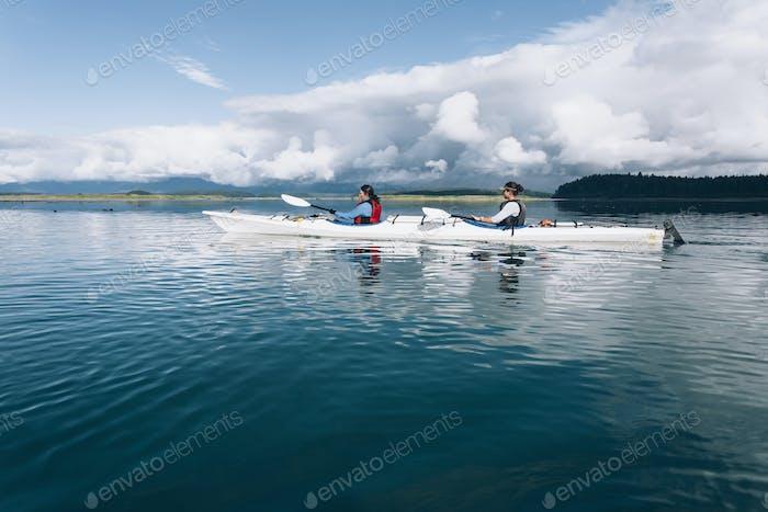 Seekajakfahrer paddeln unberührte Gewässer einer Bucht an der Küste von Alaska.