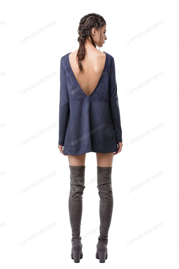 Junge Dame stehend von hinten in dunkelblauem Wildlederkleid mit Schnitt auf Rücken und kniehohen Stiefeln