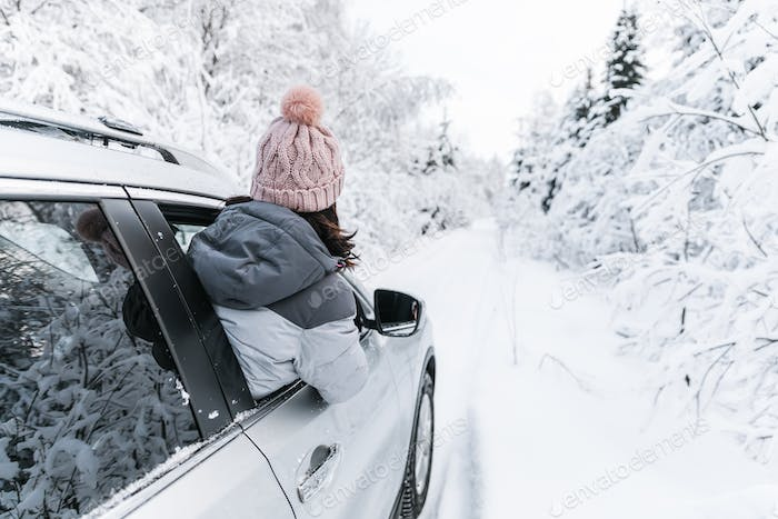 Young girl travelling in car on winter road and snow covered forest.