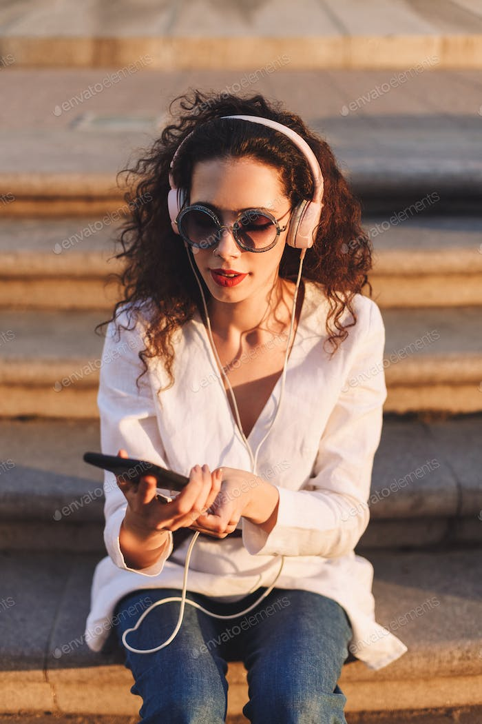 Beautiful lady in sunglasses sitting on stairs with cellphone listening music in headphones