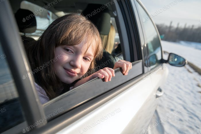 Happy little girl looking through open window in the car