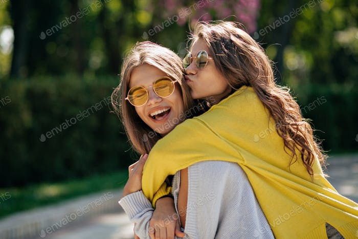 Close up lifestyle portrait of two happy inspired teen friends hugs and smiling.