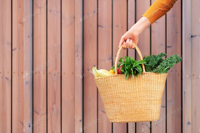 Girl holding basket with healthy organic vegetables, wooden background, copy space. Autumn harvest
