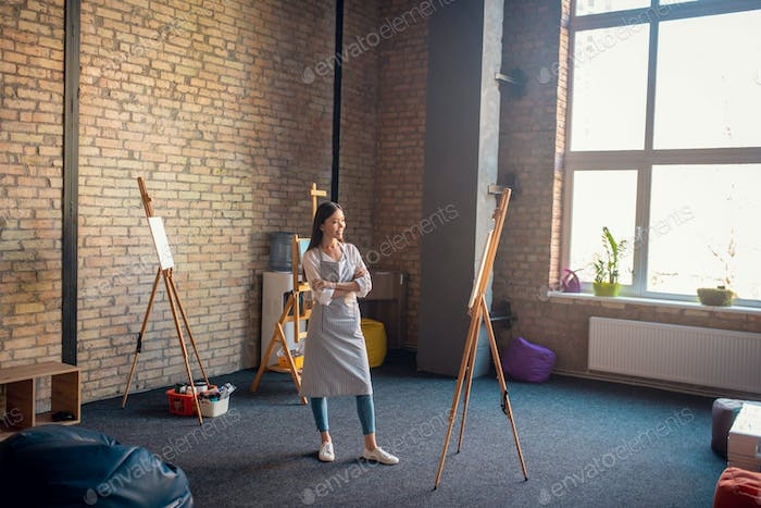 Positive happy woman looking at her artwork