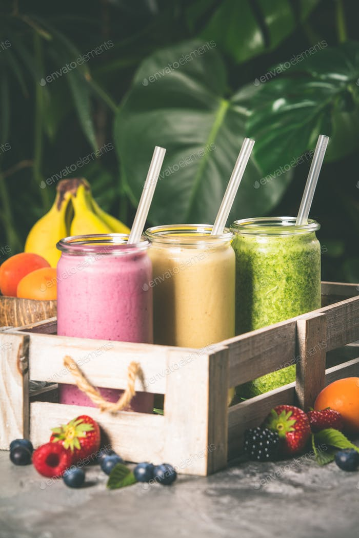 Fresh smoothies on tropical background, close up